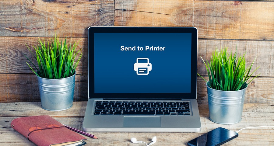 Send to printer message in a laptop screen. Wooden desk in the office.- Vegas Ink and Toner