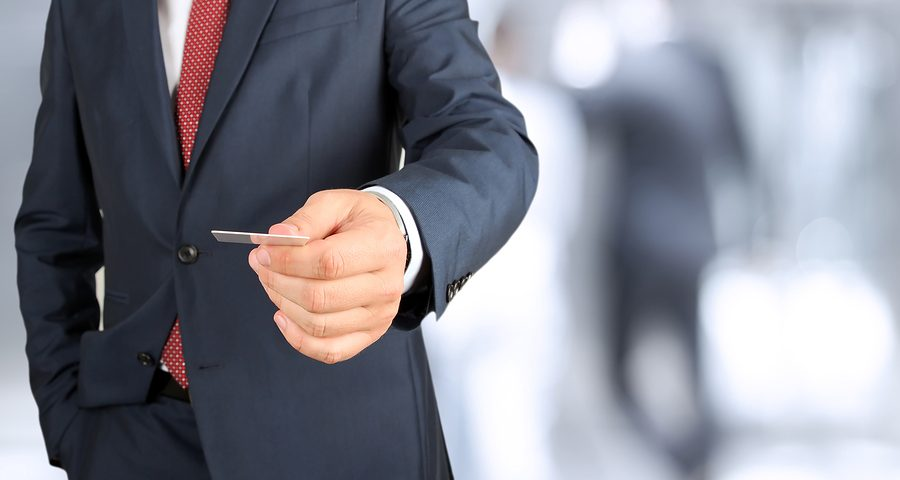 A man in a suit holding out a business card
