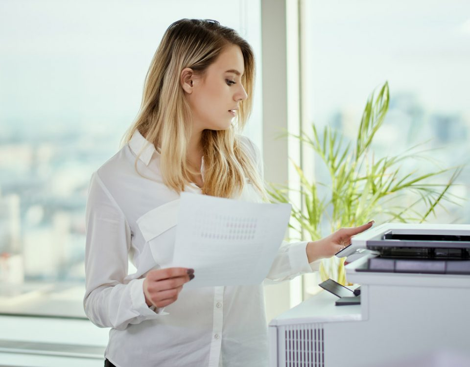A young woman using a printer in a office
