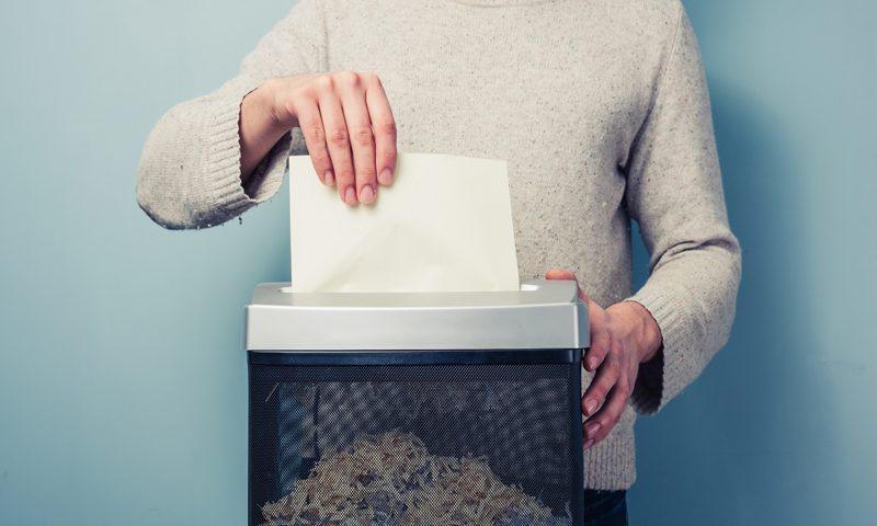 A man shredding a piece of paper