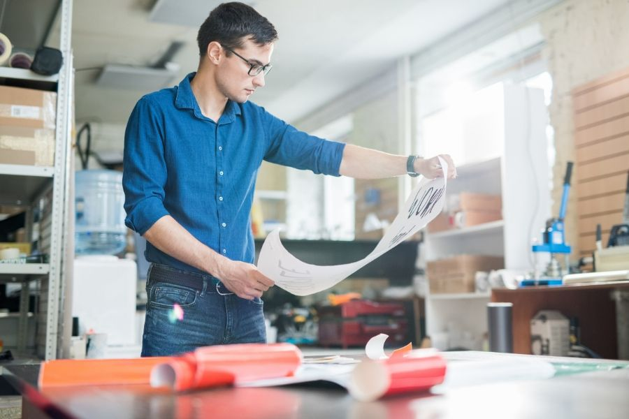Man printing paper on different sizes and weights for a project