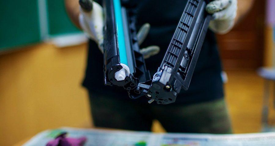 Technician Hand Cleaning Counterfeit Printer Cartridge