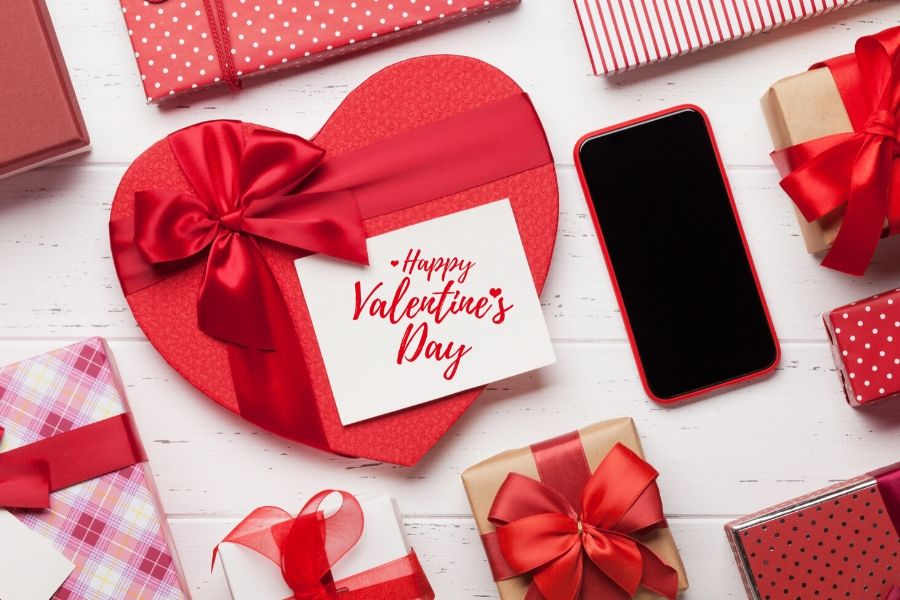 Valentines day card printed on a box of chocolates and gifts next to a phone
