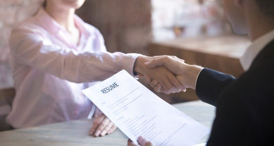 An interviewer shaking the hand of an interviewee while holding a resume