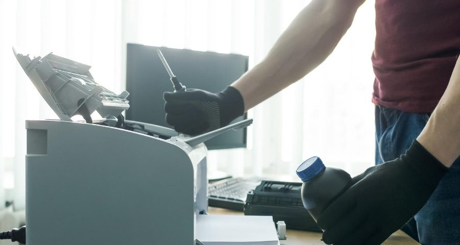 A man wearing gloves as they change out the printer toner