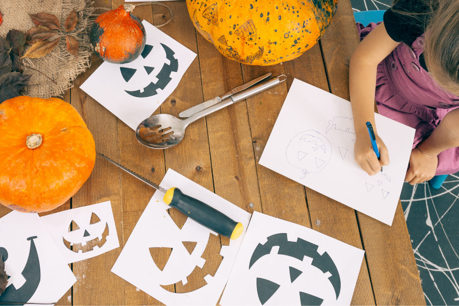 child drawing pumpkin faces
