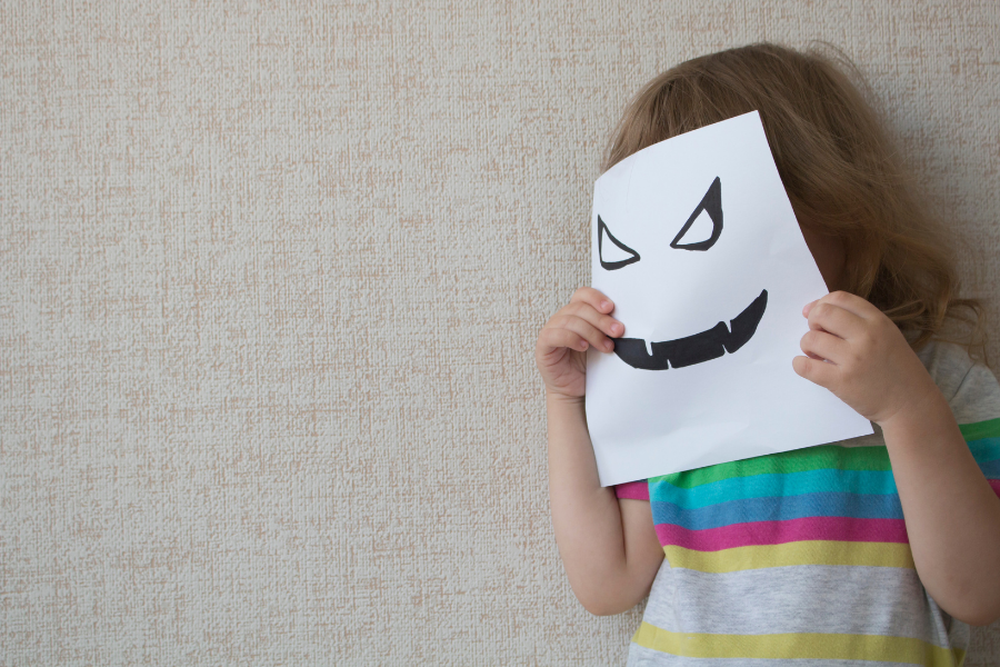 child with jack-o-lanter paper face