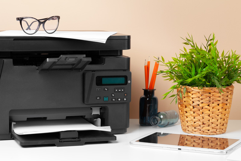 Printer with glasses on the top of it