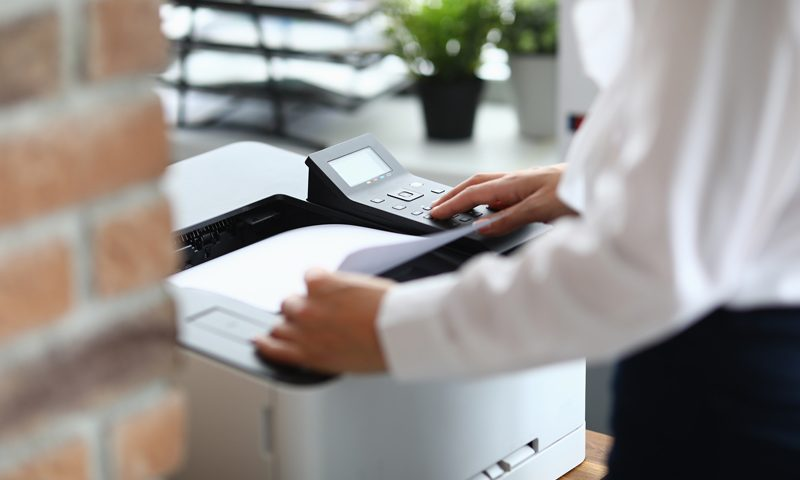 a woman using one of the best new printers of 2021